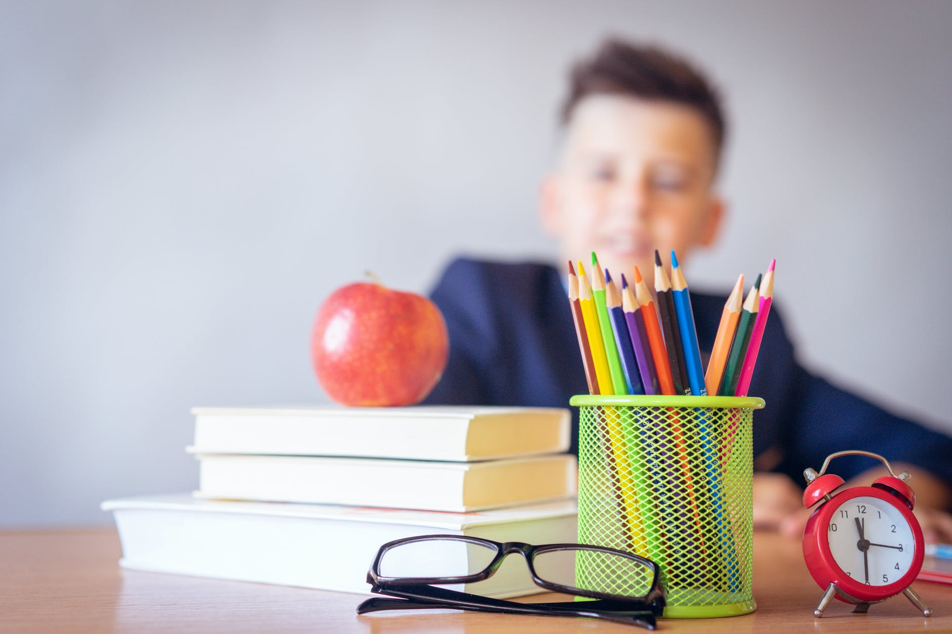 A rectangular image of a desk with a stack of books on the left-hand side, a neon green cup of colored pencils, a red alarm clock, reading glasses, with an out-of-focus silhouette of a masculine-presenting child.