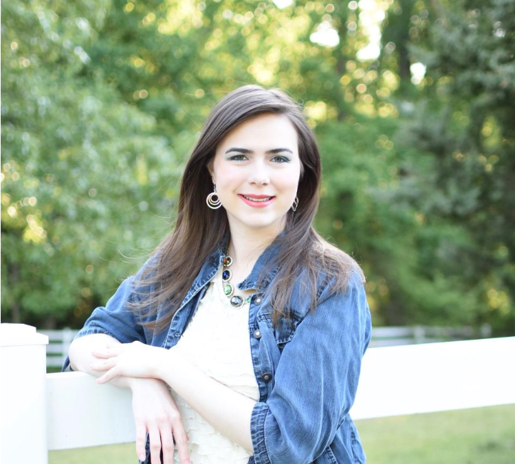 A picture of me, a white woman with dark brown hair, a jean jacket, and white blouse posed next to a white fence with trees in the background.